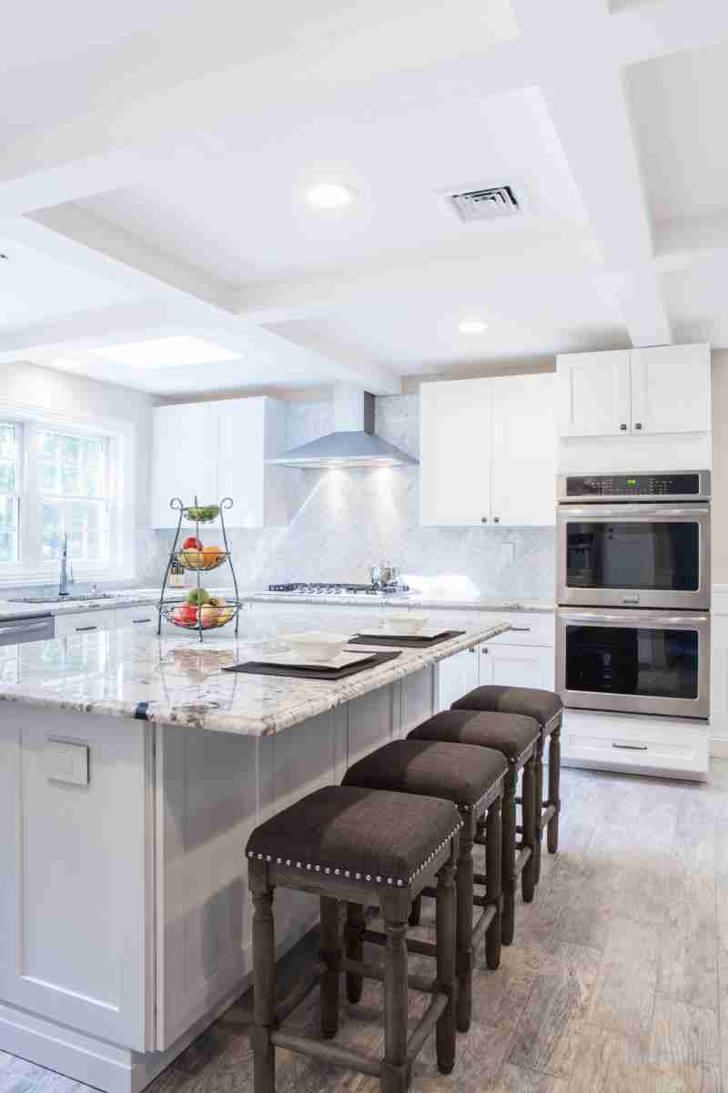J&K Cabinetry White Kitchen with Brown Chairs